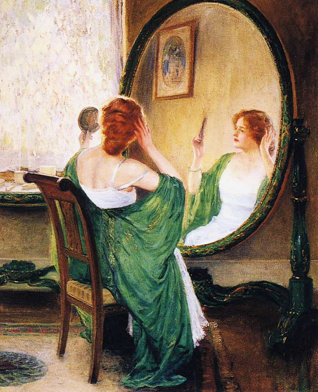 Beautiful woman with green robe on looking in large mirror