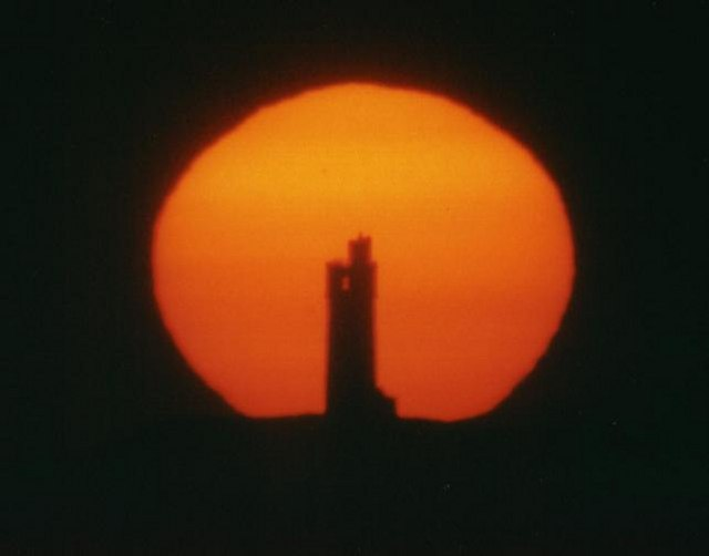 Tower against a large rising sun