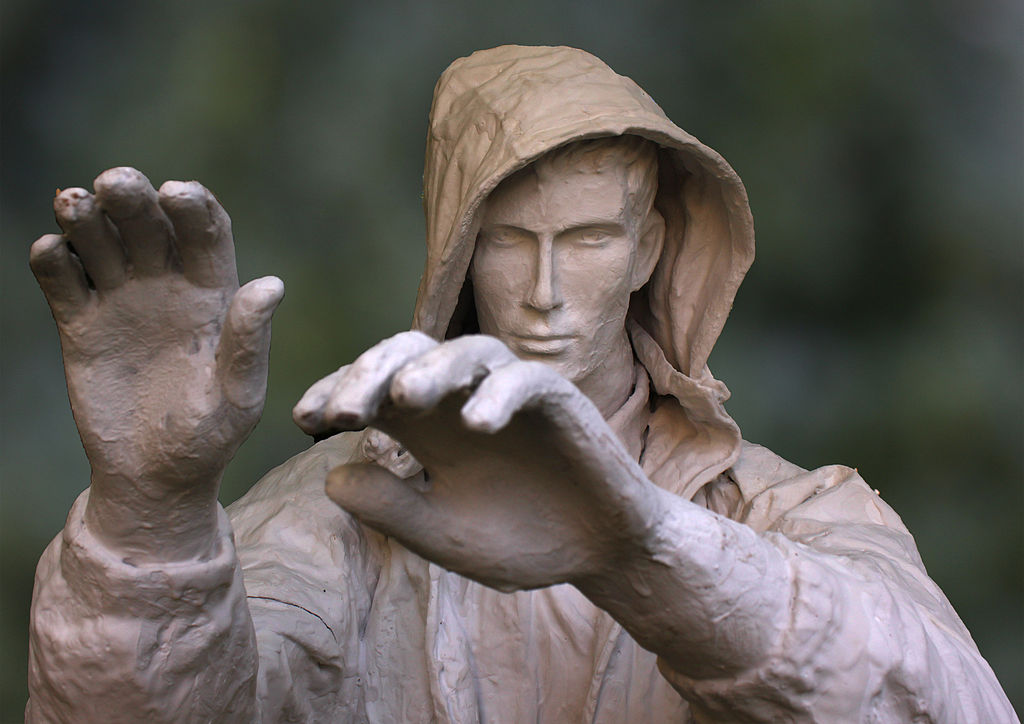 Statue of man in jacket holding up hands as if to reject something