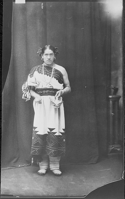 Old photograph of a Native American male of the Zuni tribe dressed in female clothing.